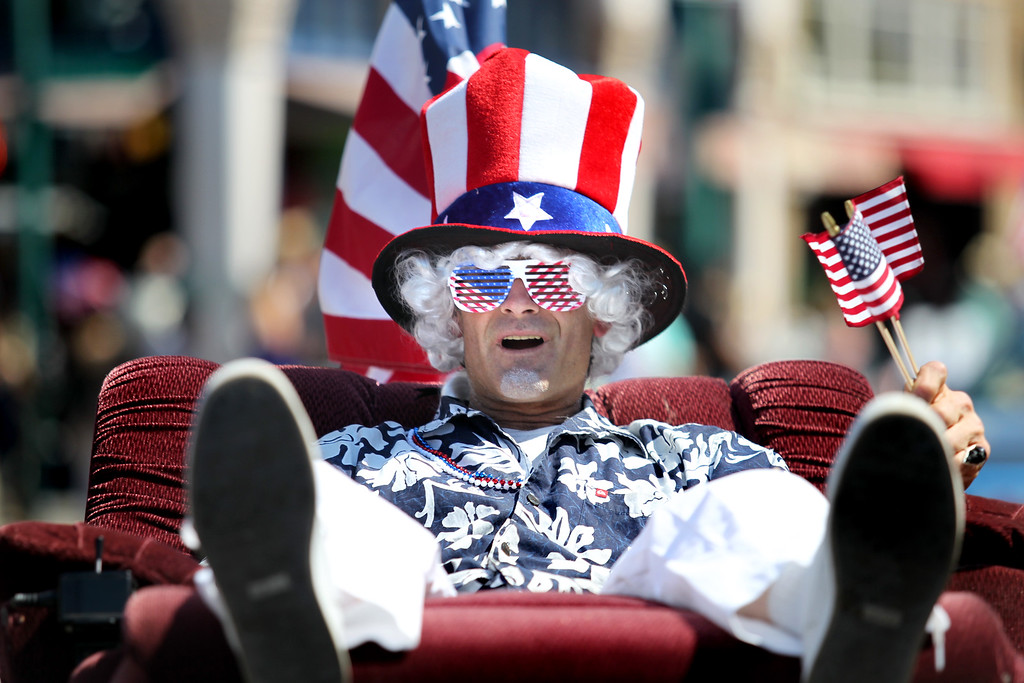 . A man on a wheeled recliner takes part in the Alameda Mayor\'s July 4th Parade on Park Street in Alameda, Calif., on Thursday, July 4, 2013. (Ray Chavez/Bay Area News Group)