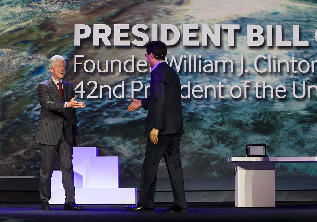. Former U.S. President Bill Clinton (L) is welcomed onstage by Stephen Woo, president of Device Solutions Business for Samsung Electronics, during a Samsung keynote address at the Consumer Electronics Show (CES) in Las Vegas January 9, 2013. (REUTERS/Steve Marcus)