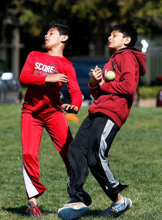 . At right, Dhaval Jani, 11, misses a catch while fielding at the cricket festival sponsored by the California Cricket Academy at the Cupertino Library Field\'s cricket pitch in Cupertino, Calif. on Saturday, March 9, 2013.  Boys and girls ages 5-13 were invited to attend and learn the basics of the game.  (LiPo Ching/Staff)