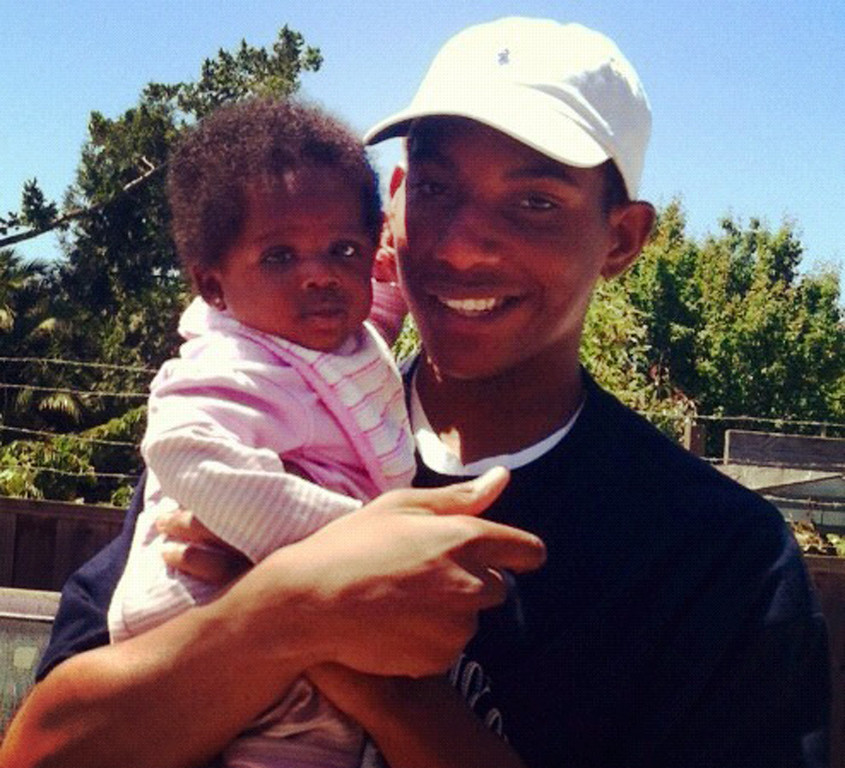 . July 10: Hadari Askari, 15, an Oakland Fire Department summer intern, was shot and killed 100 yards from the front door of his home inside the Lion Creek Crossing housing estate. A family photo shows Hadari Askari holding his niece, Cassie.   (Courtesy Anthonesha Alexander)