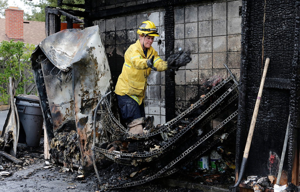 . Kathy Baker, of the Santa Clara County Fire Department, clears away rubble to find the cause of an early morning fire at the Happy Hound restaurant in Los Gatos, Calif. on Monday, March 4, 2013. The family owned restaurant has been a Los Gatos landmark for over forty years. (Gary Reyes/ Staff)