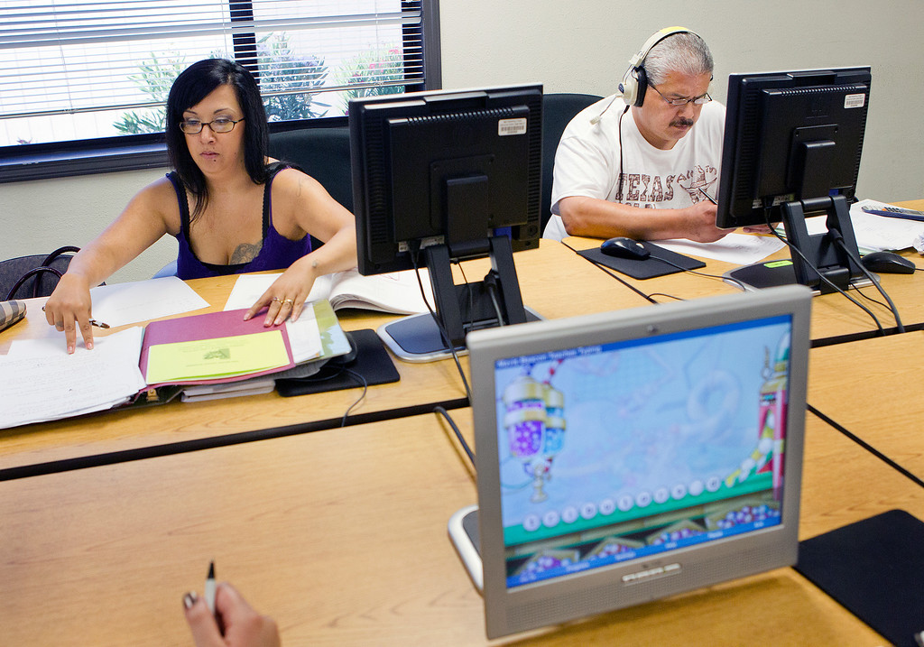 . In the foreground, Tomara Fingers, 36, (not pictured) practices typing with a typing game tutorial, as Merissa Paz, 33, left, studies for the GED writing and reading test, and Daniel Medina, 46, studies for the GED math test at the computer lab of the Metropolitan Adult Education Program (MetroED) in San Jose, Calif. on Tuesday, July 2, 2013. For the computerized GED tests, students will be required to type a minimum of 35wpm. (LiPo Ching/Bay Area News Group)