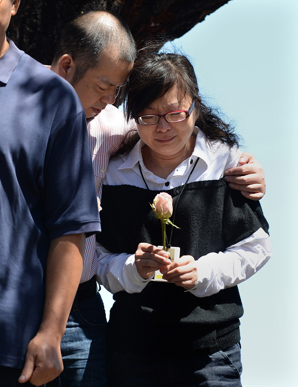 . A couple identified as the parents of Asiana crash victim Ye Mengyuan stand as an unidentified man speaks on their behalf during a prayer ceremony for the Asiana Flight victims put on by the Tzu Chi Foundation in Burlingame, Calif., on Saturday, July 13, 2013. Tzu Chi is an international Buddhist relief organization that began in Taiwan and offers compassionate efforts for charity, medical treatment, education and disaster relief.  (Dan Honda/Bay Area News Group)