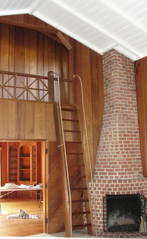 . The 1937 Berkeley Hills cabin owned by Jennifer Thomas and Rich Meyer before its 2012 remodel. In this view, the original two-sided fireplace is seen from the two-story living room, which contained a small loft space, used as a bedroom, to the left of the fireplace. The loft and ladder have been retained in the redesign, with the rail improved to code. The loft space is now used as a study. Gustave Carlson Design photo.