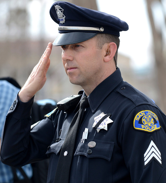 . San Jose police Sgt. Brian Shab salutes as the Santa Cruz procession arrives at the HP Pavilion in San Jose, Calif., on Thursday, March 7, 2013.  (Dan Honda/Bay Area News Group)
