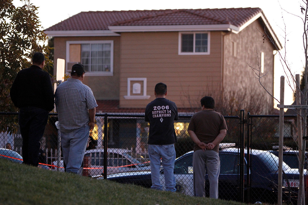 . People stand outside of a house as San Jose Police Officers investigate a double homicide at a home on the 1800 block of Bermuda Way in San Jose, Calif., on Thursday, Feb. 14, 2013.  (Nhat V. Meyer/Staff)