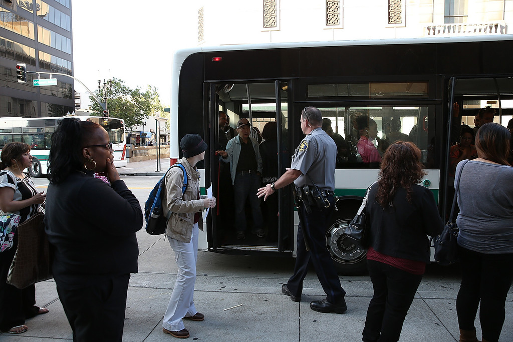 . Commuters line up as they wait to board an AC Transit bus on July 1, 2013 in Oakland, California. Hundreds of thousands of San Francisco Bay Area commuters are scrambling to find ways to work after the Bay Area Rapid Transit (BART) workers from the Amalgamated Transit Union Local 1555 went on strike at midnight after contract negotiations with management fell apart on Sunday. (Photo by Justin Sullivan/Getty Images)
