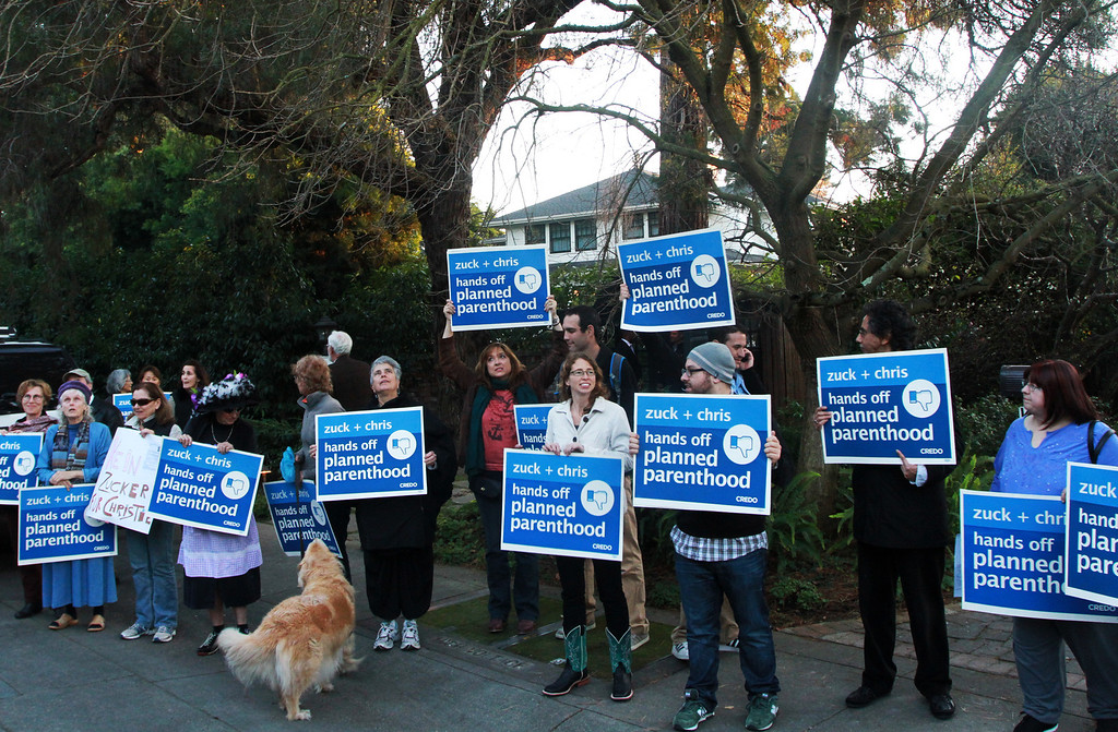 """. A group of protesters rally in front of the home of Facebook CEO Mark Zuckerberg in Palo Alto on Wednesday, Feb. 13, 2013. Zuckerberg hosted a campaign fundraiser for New Jersey Republican Gov. Chris Christie at his home Wednesday evening. About 40 protesters total demonstrated at the house; they said they were demonstrating against Christie�s visit because of his efforts to defund Planned Parenthood and other women�s reproductive health care programs. Protester and Palo Alto resident Cheryl Lilienstein said she wondered if Zuckerberg had any idea what Planned Parenthood means for women\'s health and Christie�s stances. \""""I hope he\'s just confused,\"""" she said. Zuckerberg and wife Priscilla Chan first got to know Christie after donating $100 million to struggling Newark schools two years ago, according to a Facebook spokeswoman.  (Kirstina Sangsahachart/ Daily News)"""