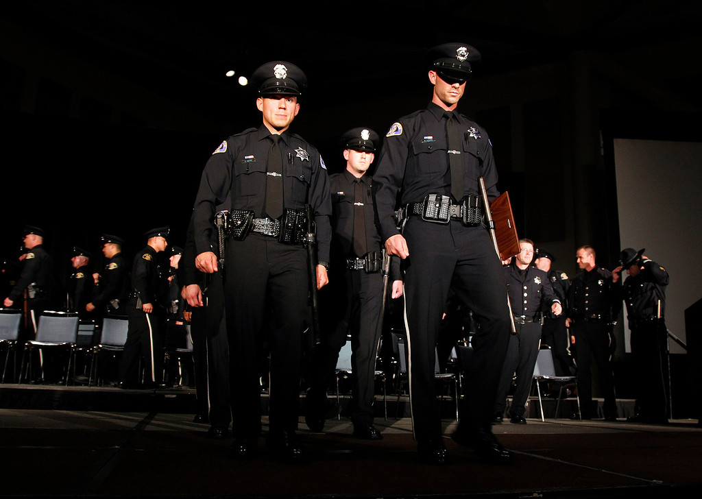 . San Jose Police Department Officers walk off the stage after the San Jose Police Academy graduation in San Jose, Calif. on Friday, March 15, 2013.   (LiPo Ching/Staff)
