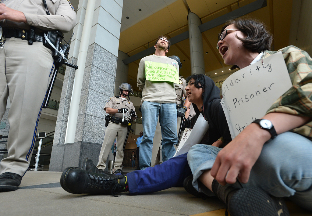 . A protester is restrained before being escorted from the lobby of the Elihu Harris state building in downtown Oakland, Calif. on Monday, Aug. 5, 2013. Seven protesters were led from the scene in riot cuffs after staging a protest in solidarity with hunger strikers in California prisons. (Kristopher Skinner/Bay Area News Group)