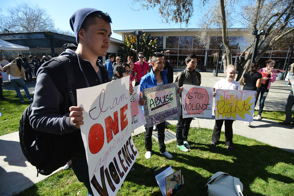". Lawrence Malloy, left, holds an anti-violence sign during a ""One Billion Rising\"" event at Diablo Valley College in Pleasant Hill, Calif. on Thursday, Feb. 14, 2013.  (Kristopher Skinner/Staff)"