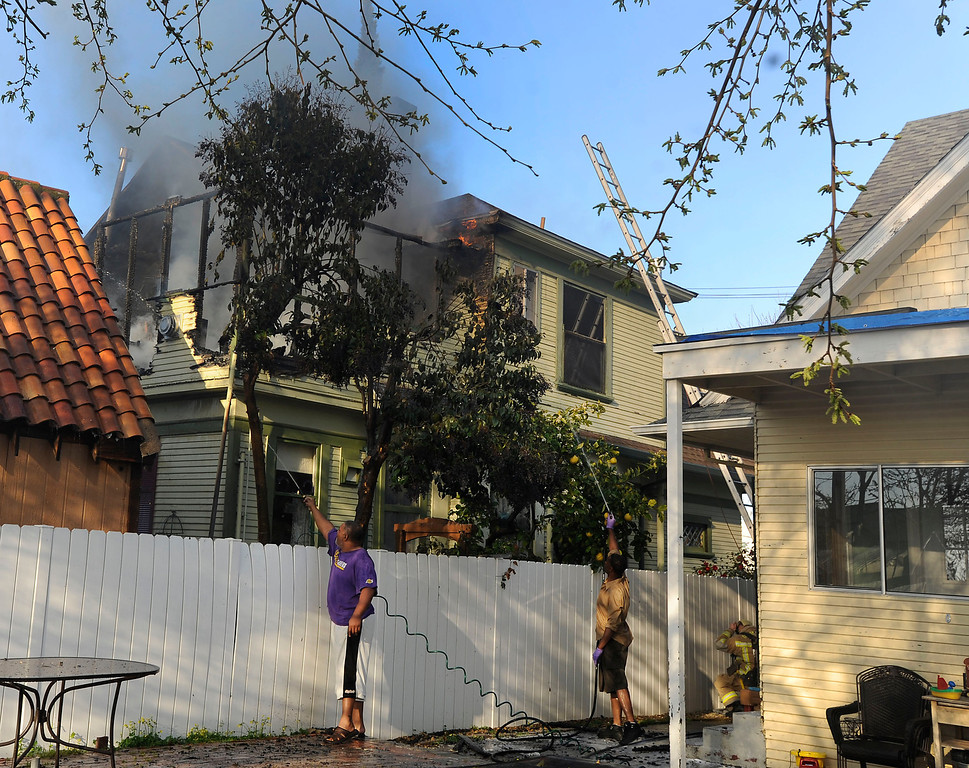. First on the scene, Jarred Allen, left and  John Lang, both of Antioch, back up as debris begins to fall as they use a neighbor\'s garden hoses to fight the structure fire in the 400 block of H Street in Antioch, Calif., on Wednesday, March 13, 2013. The men saw the flames when they were working nearby and came to help out. (Susan Tripp Pollard/Staff)