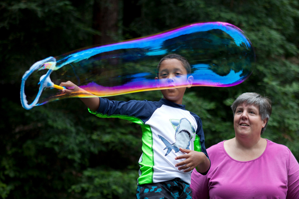. Adam Best-Leung, 7, of Alameda makes bubbles as Mollie McLeod looks on during Camp ALWAYS at Mt. Cross in Ben Lomond, Calif., Tuesday, June, 25, 2013. The camp is led by a combination of AASK (Adopt a Special Kid Agency) staff and trained counselors. (Patrick Tehan/Bay Area News Group)