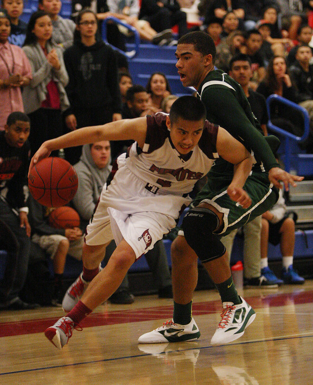 . Piedmont Hills\' JJ Espanola dribbles around Leigh\'s Devin Miller in the overtime period during the Blossom Valley Athletic League boys basketball championship game at Independence High School in San Jose, Calif. on Friday, Feb. 15, 2013. The Leigh longhorns beat the Piedmont Hills Pirates, 61-54, in overtime. (Jim Gensheimer/Staff)