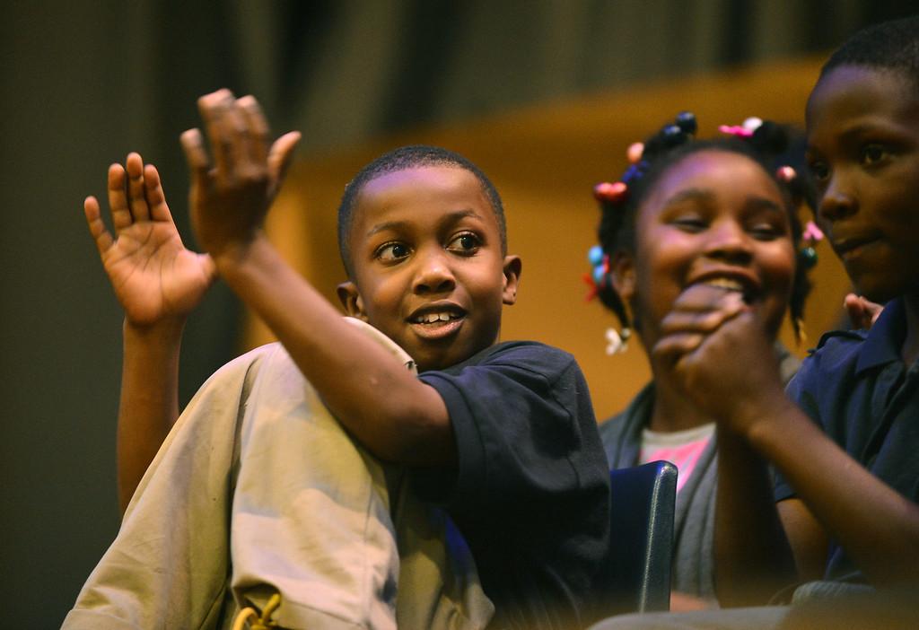 . Sankofa Academy third-grader Amani Johnson, left, applauds the effort of a fellow contestant at the school\'s second annual spelling bee in Oakland, Calif. on Wednesday, Jan. 23, 2013. (Kristopher Skinner/Staff)