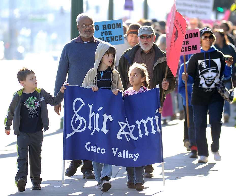 . Jason Steele, 6, Roy King, Sean Lange, 9, Hadasah Steele, 7, and Dick Albert, from left,  march in the 10th annual interfaith Martin Luther King Jr. Day march and rally in Hayward, Calif., on Monday, Jan. 21, 2013. The rally, held at the Hayward City Hall Plaza, featured words of King and music from the First United Methodist Church of Hayward, the First Tongan United Methodist of San Bruno and Congregation Shir Ami of Castro Valley.  (Doug Duran/Staff)