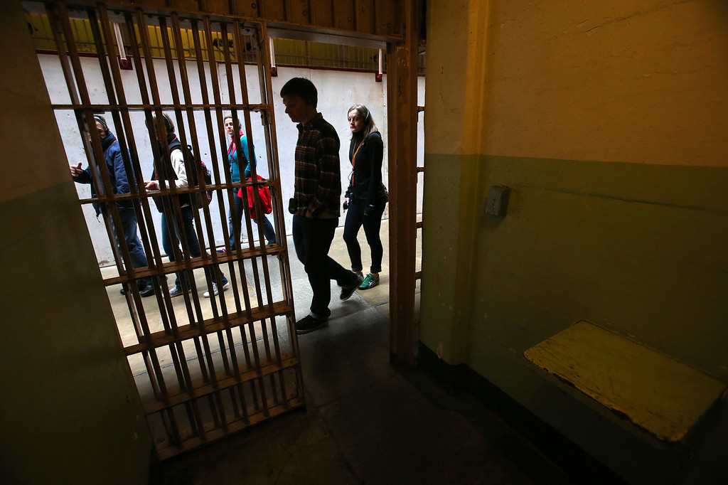 . A group of tourists walk past a prison cell on Alcatraz Island on Monday, March 18, 2013 in San Francisco, Calif. The federal prison on the island closed 50 years ago and is now a tourist destination.  (Aric Crabb/Staff)