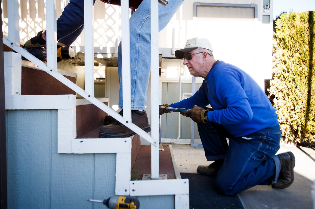 . Volunteers from Rebuilding Together Silicon Valley including Ted Anderson, right, work on replacing front steps at Maria Januzys\' mobile home on Jan. 21, 2013 in Morgan HIll. The volunteers worked on various fixes including replacing the countertop and sink, replacing her front steps, installing shelving, and more. (Dai Sugano/Staff)