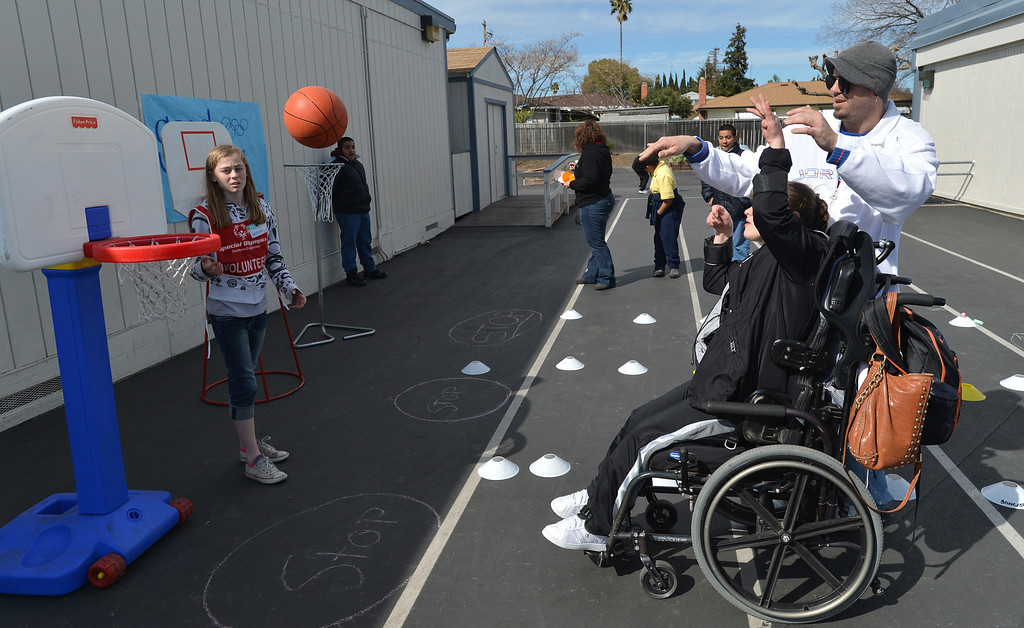 . John Place, an instructional assistant for the Contra Costa County Office of Education\'s East County Student Programs, looks on as Faith, 15, of Deer Valley High School in Antioch, shoots a basketball during a Special Olympics basketball skills event at Turner Elementary School in Antioch, Calif., on Friday March 8, 2013.  (Dan Rosenstrauch/Staff)