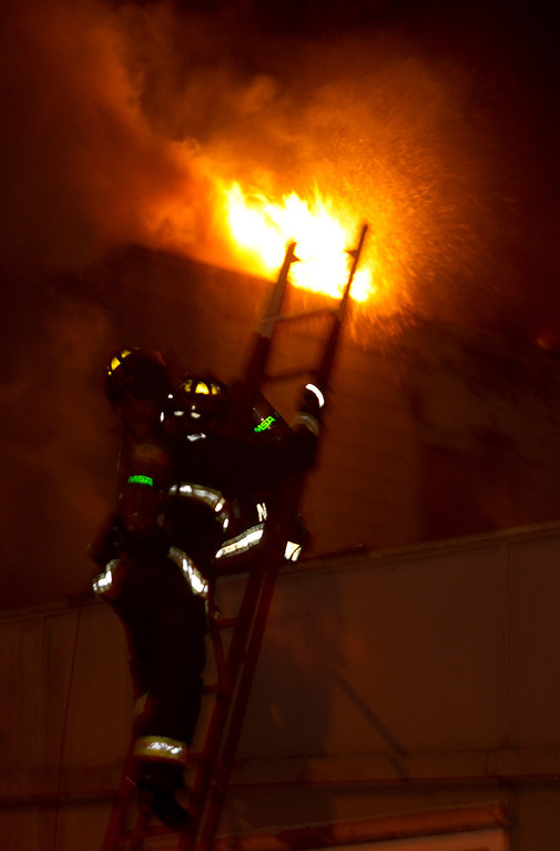 . Firefighters climb a ladder to try to quell the flames from a fire inside a vacant, wood-framed house on Harrison Street near 7th Street, Wednesday, Jan. 23, 2013 in Oakland, Calif. The building, which fire investigators said was built in 1896, caught fire when squatters inside it tried to cook food over an open flame. (D. Ross Cameron/Staff)