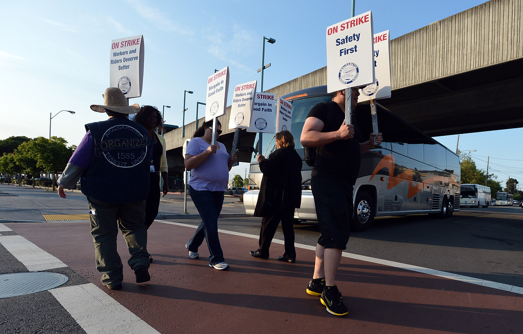 . Union workers slowly walk the picket line as a bus carrying commuters exits the West Oakland BART station in Oakland, Calif. on Monday, July 1, 2013. (Kristopher Skinner/Bay Area News Group)