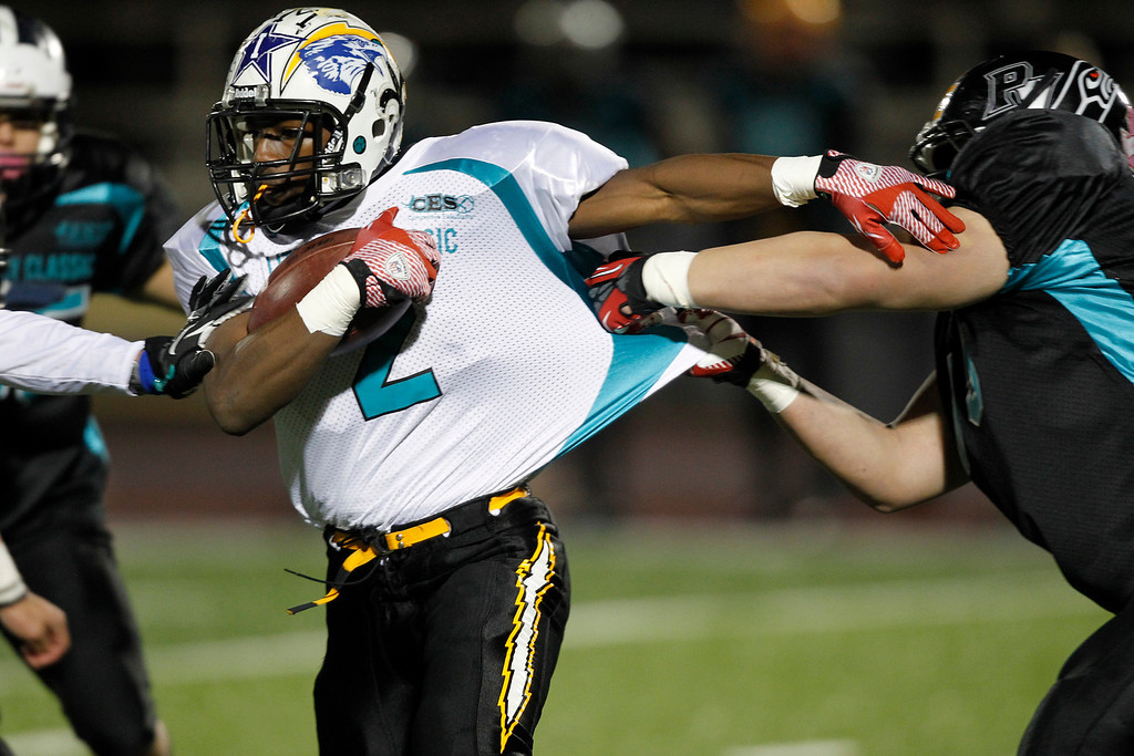 . North\'s Roland Luke makes a run as the South\'s Jonathan Tuiolosega pulls on his jersey in the first quarter of the Literacy All-Star high school football game at San Jose City College in San Jose, Calif. on Saturday, Jan. 26, 2013. (Jim Gensheimer/Staff)
