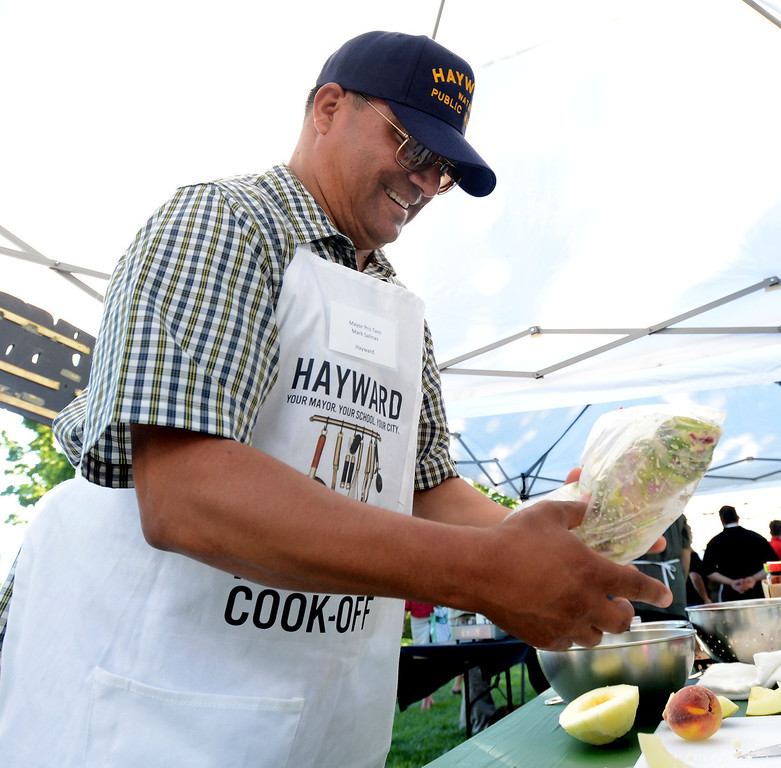 """. Hayward Mayor Pro Tem Mark Salinas, prepares a chicken marinade during the \""""Alameda County Mayors\' Healthy Cook-Off Challenge\"""" held at the Dublin Farmers\' Market at Emerald Glen Park in Dublin, Calif., on Thursday, July 25, 2013. The Hayward team, consisting of Chef Tony Solorio with the Hayward\'s Tacos Uruapan restaurant, went on to place second, advancing them to compete against the winners of the Contra Cost County Mayors\' Healthy Cook-Off Challenge. The contest will be held at Mt. Diablo High School in the fall. The cook-off was presented by Concord\'s Wellness City Challenge and promotes the importance of healthy eating. (Doug Duran/Bay Area News Group)"""