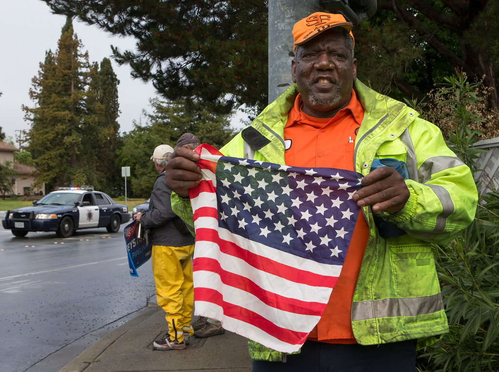 . An Obama supporter, who did not want his name used, holds an American flag on Alameda de las Pulgas as he waits for the presidential motorcade to pass en route to a fundraising event in Atherton, Calif., on Thursday, April 4, 2013. (John Green/Staff)