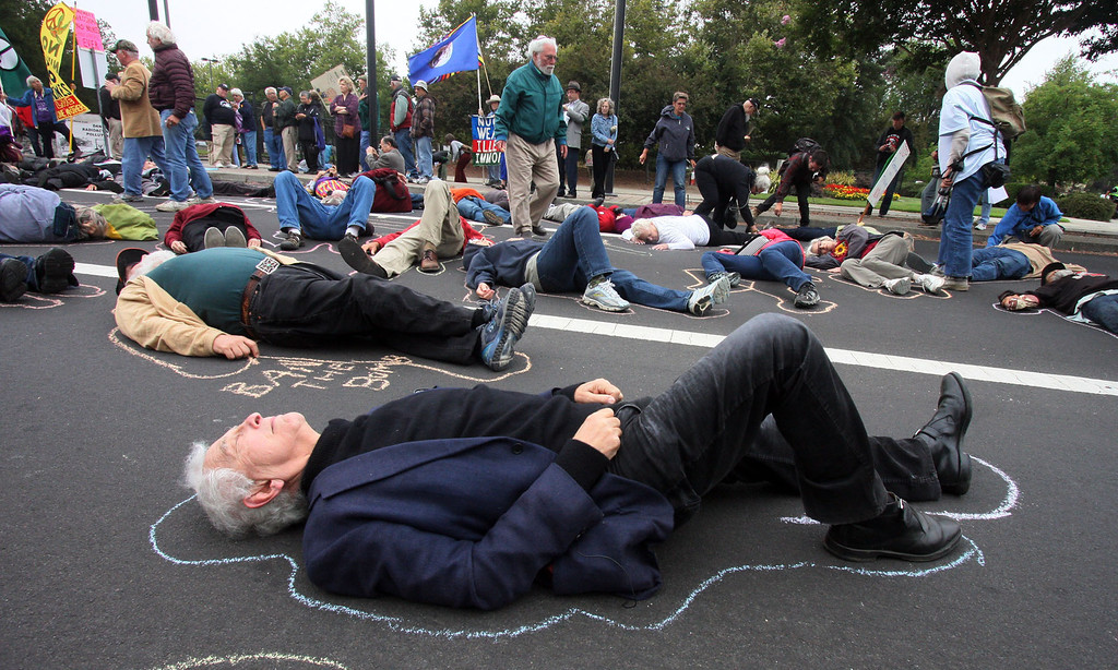 . Daniel Ellsberg lies on the street with other protesters in Livermore, Calif., on Tuesday, Aug. 6, 2013. The chalk outlines represent the vaporized bodies of victims of the atomic bomb blasts in Japan. Ellsberg was  later arrested by an officer from Lawrence Livermore Laboratory\'s protective forces at the protest at LLNL.   (Jim Stevens/Bay Area News Group)