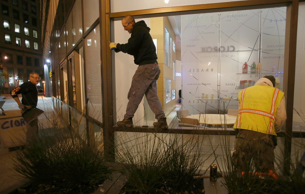 . Workers board up smashed windows at the Wells Fargo Bank on Broadway and 12th Street in downtown Oakland, Calif., early Sunday, July 14, 2013. Protesters also lit several small fires on Telegraph Avenue and sprayed graffiti after learning that George Zimmerman had been found not guilty in the shooting death of Trayvon Martin in Sanford, Fla. (Jane Tyska/Bay Area News Group)
