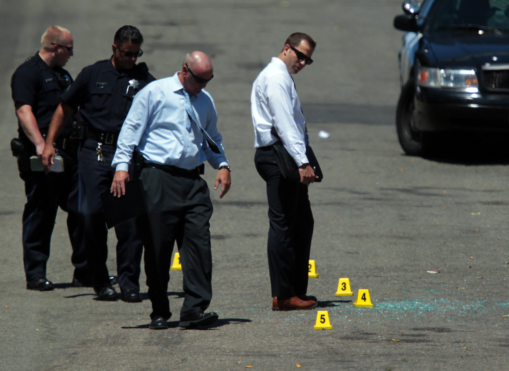 . Oakland police investigate the scene of a fatal shooting along the 2400 block of Fern Street near Fairfax Avenue in Oakland, Calif., on Wednesday, July 24, 2013. According to police, the victim, Judy Salamon, 66, was apparently shot while in her vehicle, causing the car to collide with another parked car. (Anda Chu/Bay Area News Group)