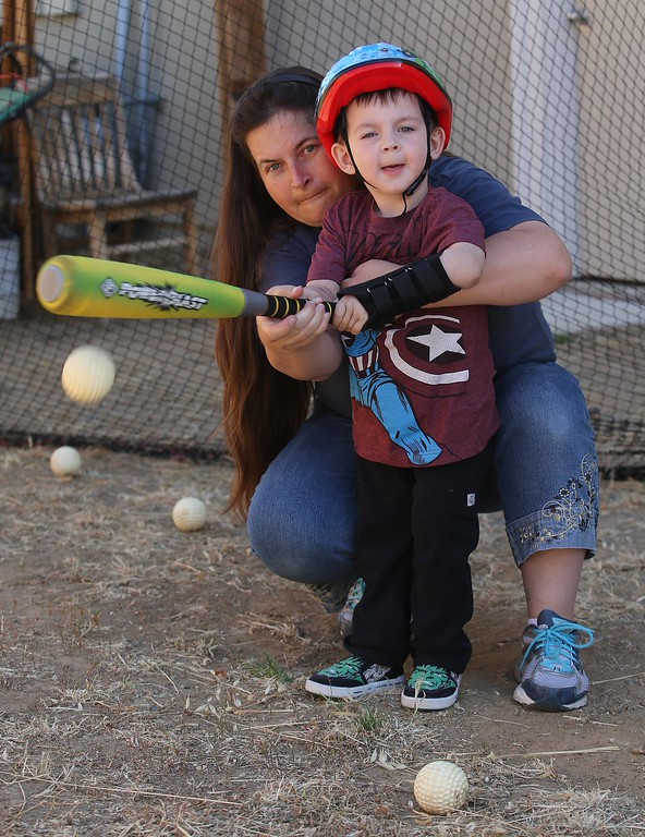 . Matthew Ouimet, 3, bats with the help of his mom Kristi Ouimet at their home in Antioch, Calif., on Thursday, May 22, 2014. (Jane Tyska/Bay Area News Group)