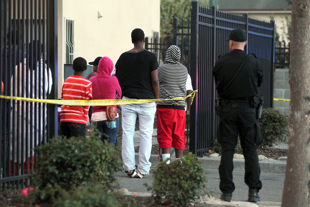 . An officer from the Oakland Housing Authority Police Department stands guard as residents look on the fatal crime scene at Mandela Parkway and 10th Street in Oakland, Calif., on Friday, Aug. 2, 2013. (Ray Chavez/Bay Area News Group)
