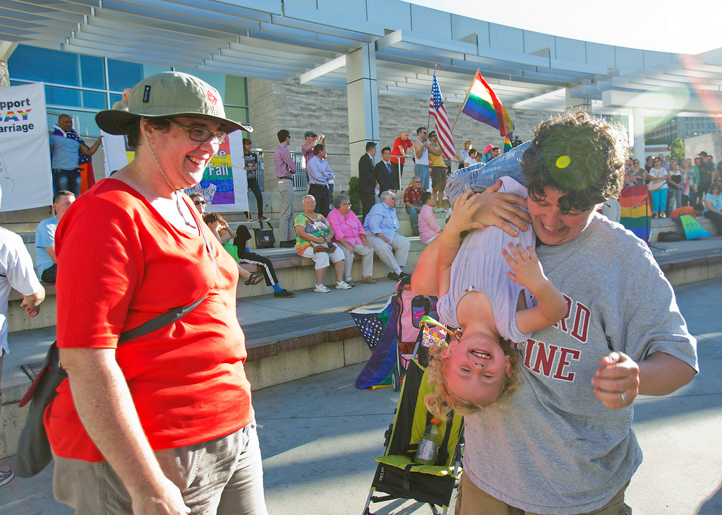 . Sarah Lester, left, and Michelle Cook play with their daughter Aurora Lester-Cook, 1, at a San Jose City Hall rally to celebrate the U.S. Supreme Court decision on DOMA and Proposition 8, in San Jose, Calif., on Wednesday, June 26, 2013. (LiPo Ching/Bay Area News Group)