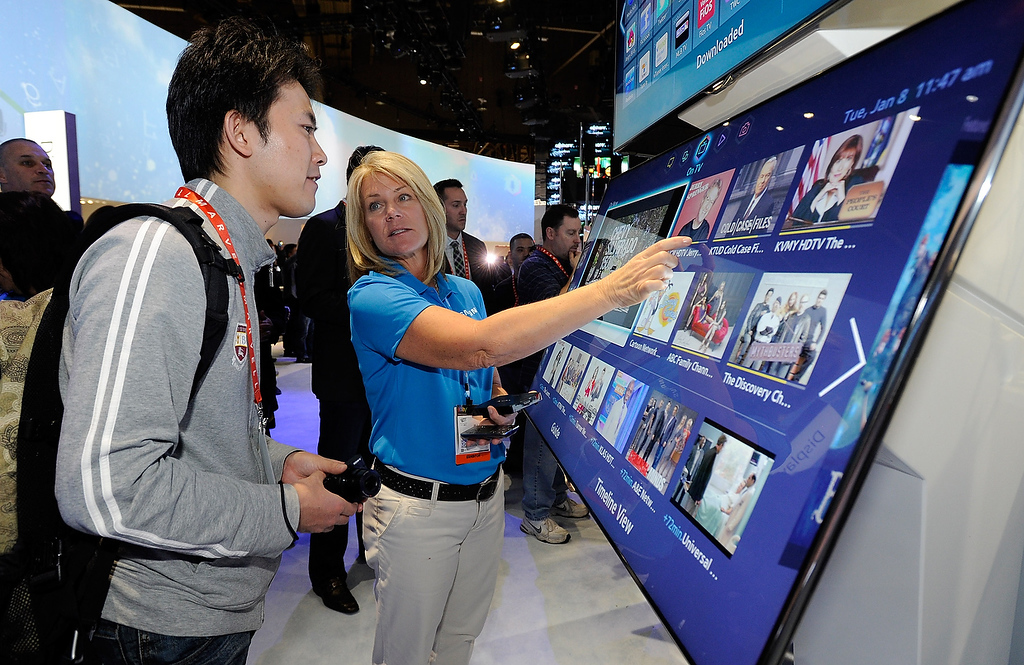 . Samsung representative Jill McKenzie helps an attendee with Samsung\'s Smart Hub at the 2013 International CES at the Las Vegas Convention Center on January 8, 2013 in Las Vegas, Nevada. (Photo by David Becker/Getty Images)