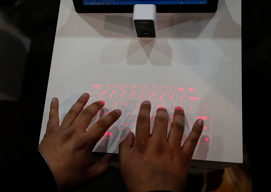 . Alvaro Patino tries out Celluon\'s Magic Cube, a projection keyboard for mobile devices at the International Consumer Electronics Show in Las Vegas, Wednesday, Jan. 9, 2013. (AP Photo/Jae C. Hong)