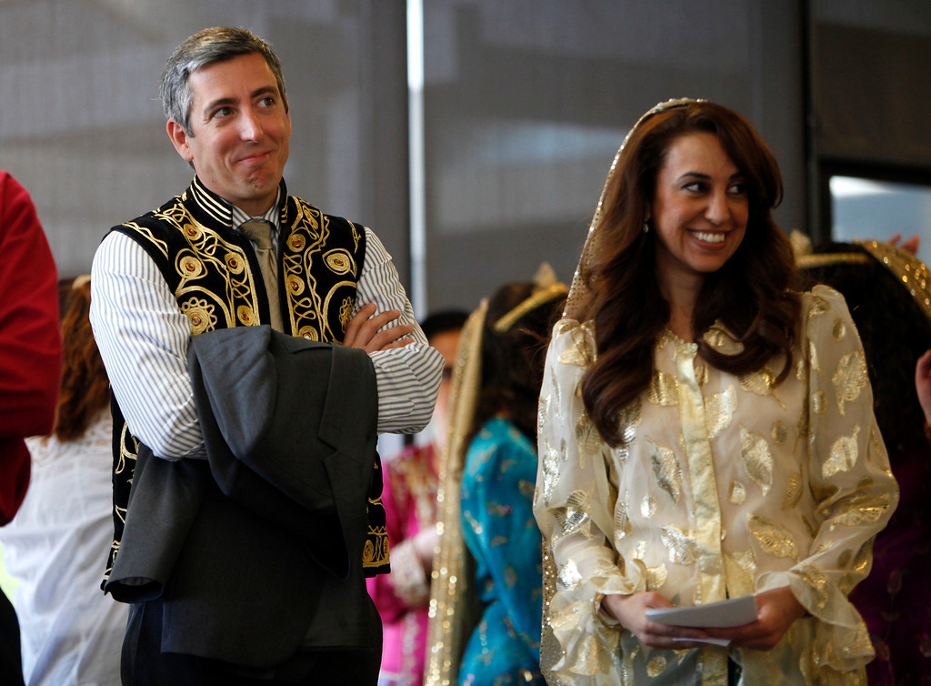 . West Valley College president Bradley Davis, left, while wearing a traditional vest, stands next to master of ceremonies Renee Paquier during the West Valley College 6th Annual Persian New Year Celebration at the college in Saratoga, Calif. on Monday, March 10, 2014.  (Nhat V. Meyer/Bay Area News Group)