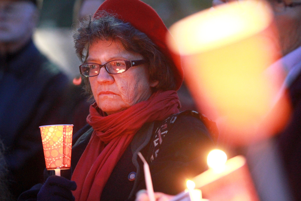 """. Stephanie Enos listens to a speech during a candlelight vigil in Lytton Plaza in downtown Palo Alto supporting an end to gun violence on Friday, Feb. 22, 2013. About 100 people attended the vigil. Organizing for Action: Silicon Valley sponsored the vigil as part of a national grassroots day of action against gun violence and to rally support for new gun control laws. �Our society is suffering from this horrible devastation of gun violence. It\'s not only the victims but the whole community and families,\"""" said Bonnie Bernstein, with Silicon Valley Community Against Gun Violence. (Kirstina Sangsahachart/ Daily News)"""