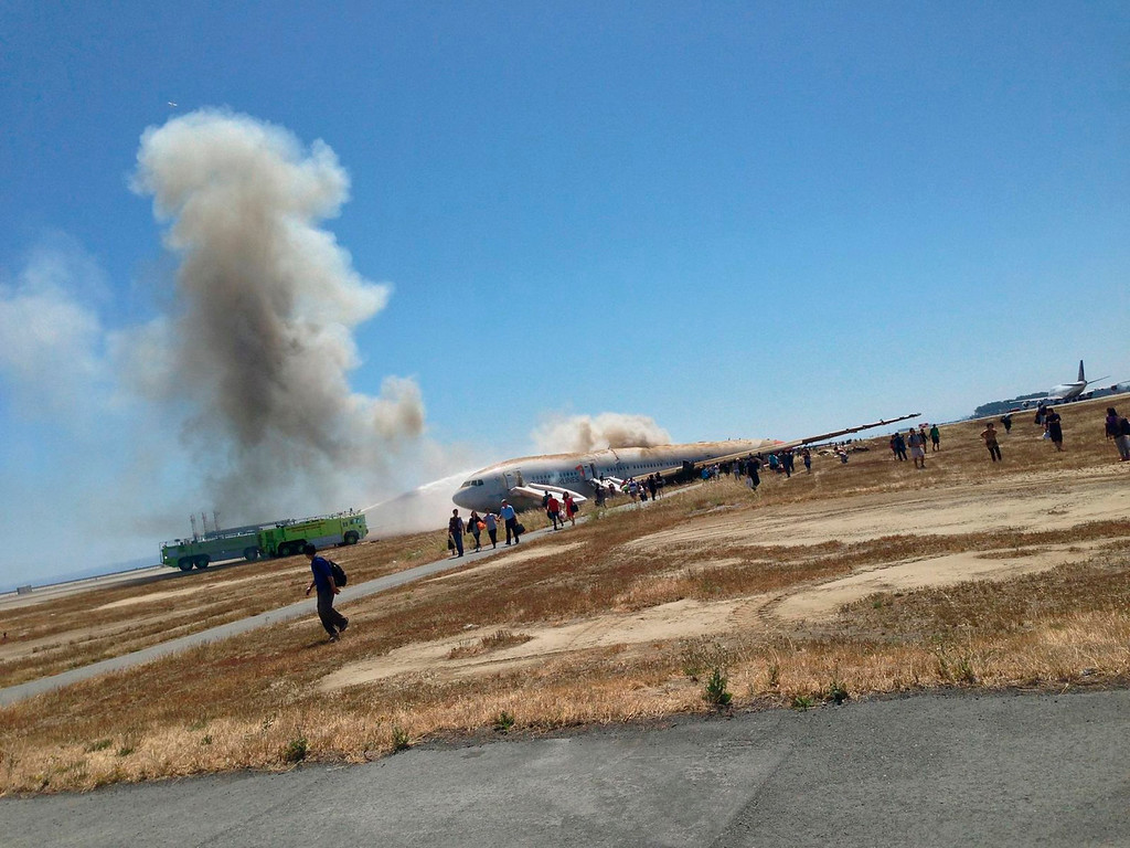 . Passengers evacuate from Asiana Airlines Boeing 777 aircraft after a crash landing at San Francisco International Airport in San Francisco, Calif. on July 6, 2013. (Eugene Anthony Rah via Reuters)i