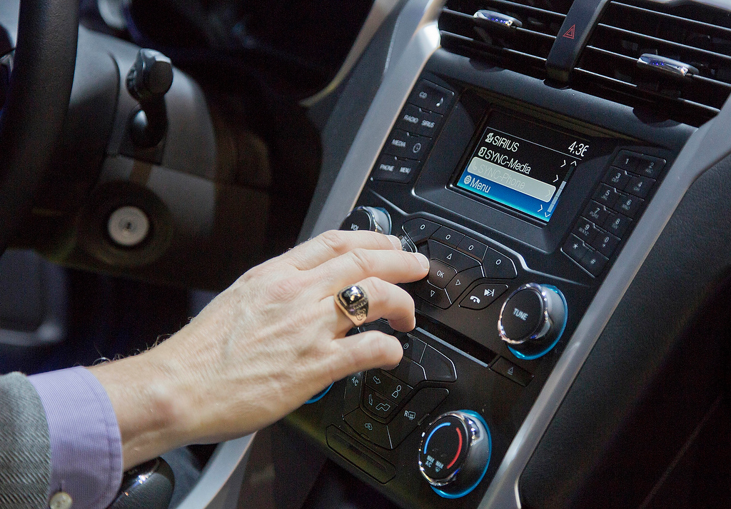 . An industry affiliate tests out Ford\'s SYNC connection and entertainment system inside a Ford Fusion at the Consumer Electronics Show, Wednesday, Jan. 9, 2013, in Las Vegas. Ford\'s SYNC connects the car stereo and navigation system to a user\'s mobile device. (AP Photo/Julie Jacobson)