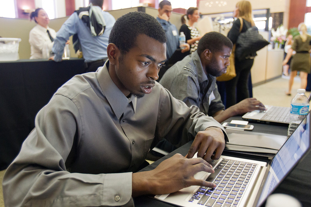 . From left, Eric Sykes and Emmanuel Carter begin the application process for Best Buy at a hiring fair hosted by TeenForce and the San Jose Silicon Valley (SJSV) Chamber at the SJSV Chamber offices in San Jose, Calif. on Wednesday, June 26, 2013.  (LiPo Ching/Bay Area News Group)