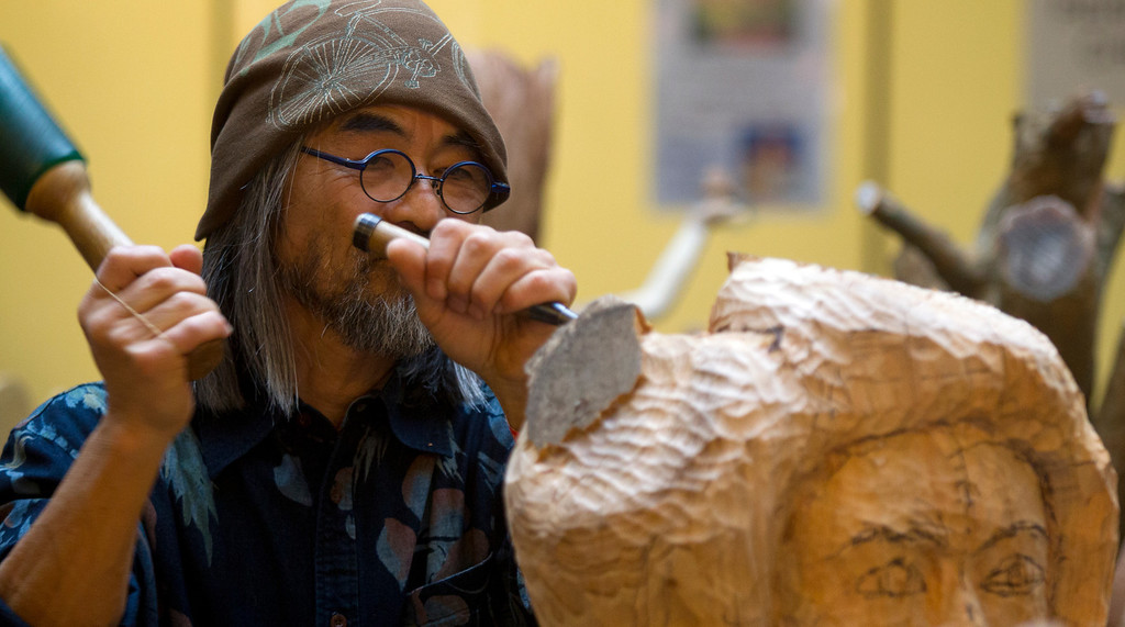 . Wood carver Takayuki Zoshi of Sebastapol, Calif. works on a carving of a woman\'s head while demonstrating his skills at the Oakland Museum of California\'s Lunar New Year celebration, Sunday, Feb. 17, 2013 in Oakland, Calif. (D. Ross Cameron/Staff)