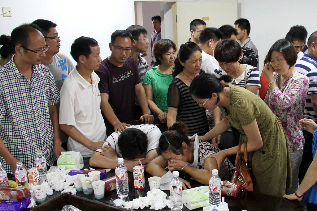 . Parents of Wang Linjia, center, are comforted by parents of some other students who were on the Asiana Airlines Flight 214 that crashed at San Francisco International Airport, at Jiangshan Middle School in Jiangshan city, in eastern China\'s Zhejiang province, Sunday July 7, 2013. Chinese state media have identified the two people who died in the plane crash at San Francisco International Airport on Saturday as Ye Mengyuan and Wang Linjia, students at Jiangshan Middle School in China\'s eastern Zhejiang province. (AP Photo)  CHINA OUT