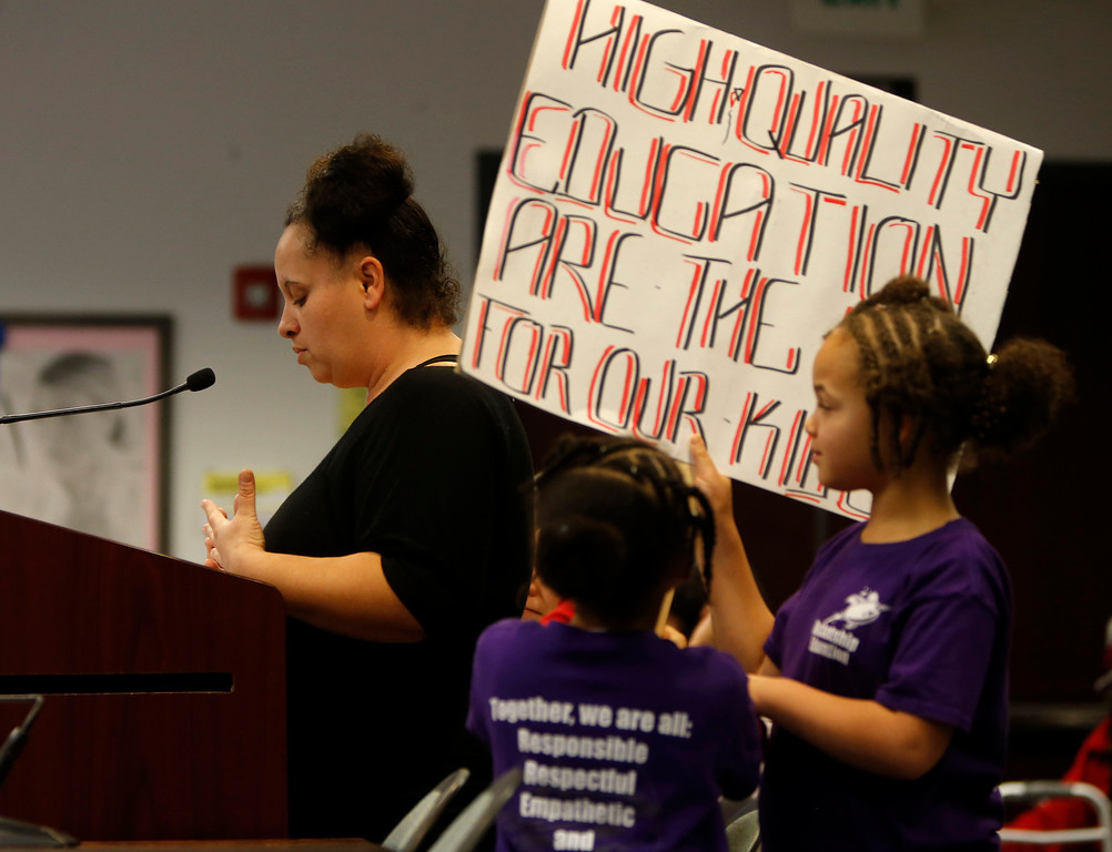 . Dione Johnson-Tyson talks to the Santa Clara County Board of Education during public comment regarding Rocketship Education\'s petition to open a new school during a board meeting at the Santa Clara County Office of Education San Jose, Calif. on Wednesday, Jan. 23, 2013.  Next to her are her daughters Souljah Johnson-Tyson, 5, and Mecca Johnson-Tyson, 7.  (Nhat V. Meyer/Staff)
