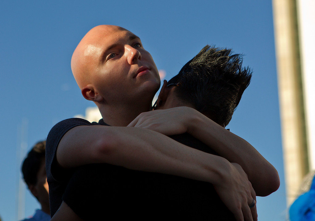 . From left, Dana Depew hugs Angelo Soriano at a San Jose City Hall rally to celebrate the U.S. Supreme Court decision on DOMA and Proposition 8, in San Jose, Calif. on Wednesday, June 26, 2013. (LiPo Ching/Bay Area News Group)