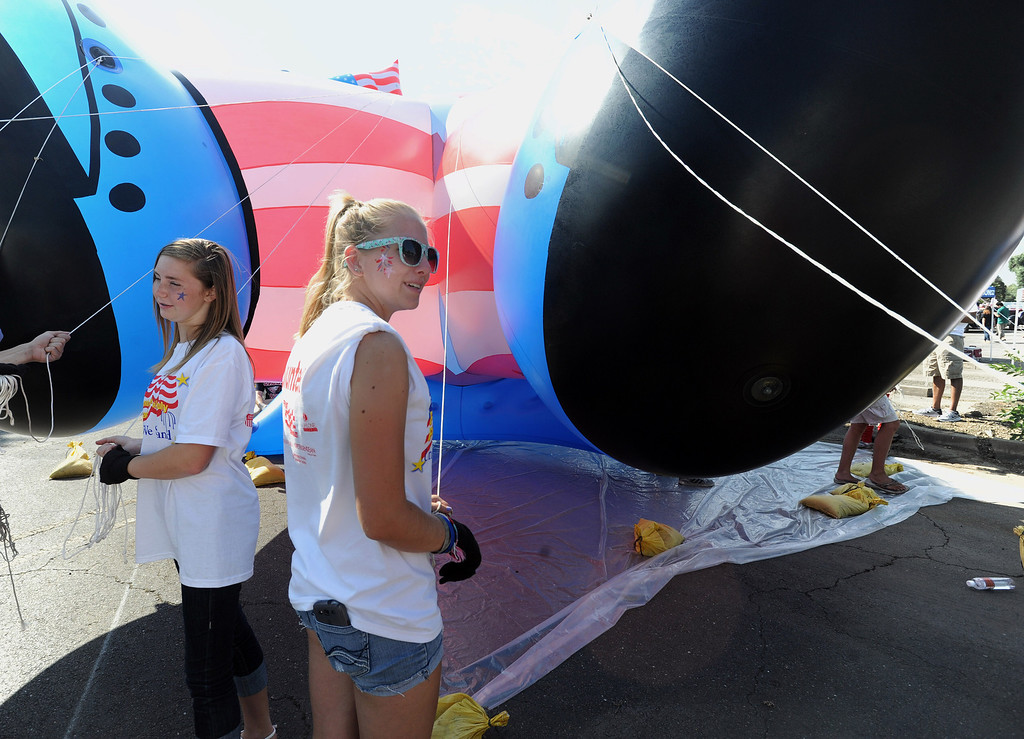 . Volunteers Emily Eitel, right, 18, of Fremont, and Hannah Mills, left, 14, of Newark, practice maneuvering a large inflated figure just prior to the start of the Fourth of July parade in Fremont, Calif., on Thursday, July 4, 2013. The parade featured more than 70 entries. (Dan Honda/Bay Area News Group)