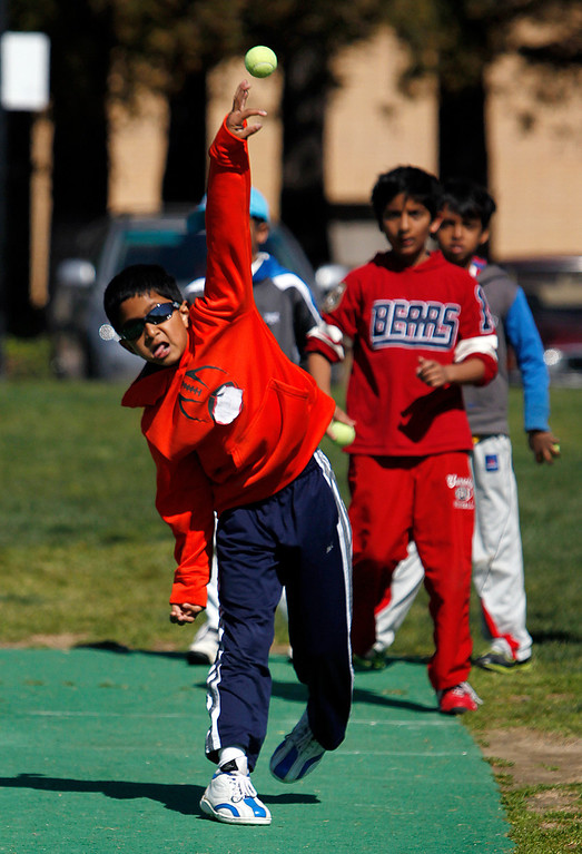 . Ved Patel, 9, practices bowling at the cricket festival sponsored by the California Cricket Academy at the Cupertino Library Field\'s cricket pitch in Cupertino, Calif. on Saturday, March 9, 2013.  Boys and girls ages 5-13 were invited to attend and learn the basics of the game.  (LiPo Ching/Staff)