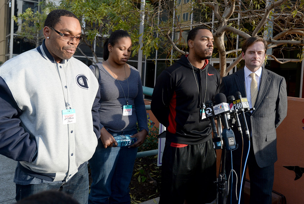 . Omari Sealey, second from the right, talks to the media, along with attorney Chris Dolan, right, Nailah Winkfield, and Milton Winkfield, far left, in front of Oakland\'s Children\'s Hospital in Oakland, Calif., on Tuesday, Dec. 17, 2013. Winkfield and McMath\'s daughter Jahi McMath, 13, was declared brain dead following complications from a three-part surgery to remove her tonsils and clear tissue from her nose and throat to treat her sleep apnea and other health issues.  (Dan Honda/Bay Area News Group)